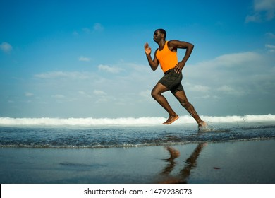 athletic full body portrait of young attractive and fit black African American man running on the beach doing Summer fitness jogging workout at the sea in sport exercise and healthy lifestyle