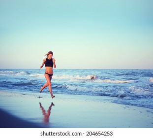 Athletic girl  with beautiful muscular body runs along the sea, evening jog on the beach, beautiful sporty girl reflected with waves on the sand, fitness and healthy lifestyle concept