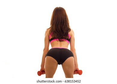 athletic girl in black shorts with beautiful buttocks stands with her back to the camera and makes the slopes with dumbbells