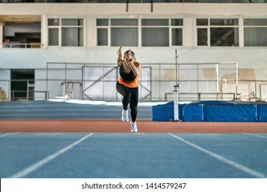 Athletic girl in a black-orange T-shirt with dark pants and gray sneakers starts her sprint run with a long jump on the running track at the indoor stadium. She looks forward. Horizontal.
