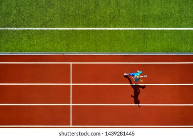 Athletic girl in a blue sportswear and sneakers runs on the running track at the stadium outdoors. Sun shines onto her body. Top view aerial photo. Horizontal.