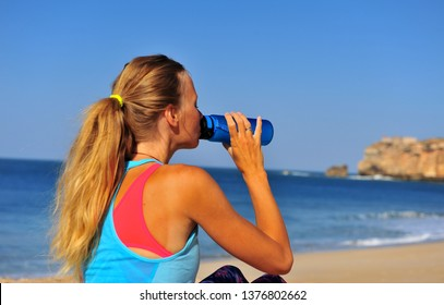 Athletic girl drinking water on beach after workout