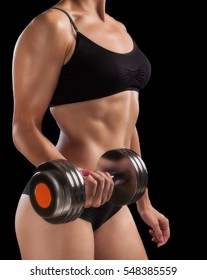 Athletic girl with dumbbells in hand.