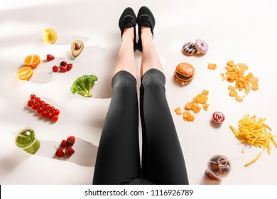 Athletic girl with healthy and unhealthy food on floor. Top view on white studio background. Sport, fitness, healthy, diet concept with copy space