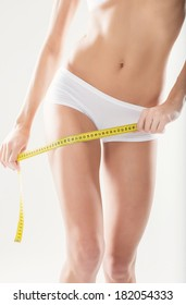 Athletic girl measuring yourself figure yellow meter
