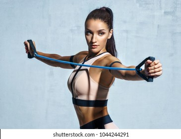 Athletic girl performs exercises using a resistance band. Photo of young girl on drey background. Strength and motivation