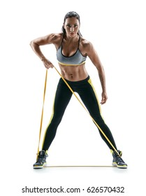 Athletic girl performs exercises using a resistance band. Photo of young girl isolated on white background. Strength and motivation