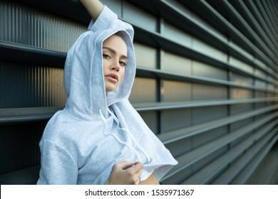 Athletisches Mädchen posiert in einer Stadt. Das Modell hat einen leichten Trackanzug, Kapuze, Turnschuhe. Stilvolle Sportaufnahmen auf der Straße. Ein schöner athletischer Körper, Gesicht, Haut, Lippen. Ein Mädchen mit bedrohlichem Aussehen.