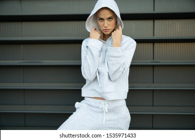 Athletic girl posing in an urban city. The model has a light tracksuit, hood, sneakers. Stylish sports shooting on the street. A beautiful athletic body, face, skin, lips. A girl with a menacing look.