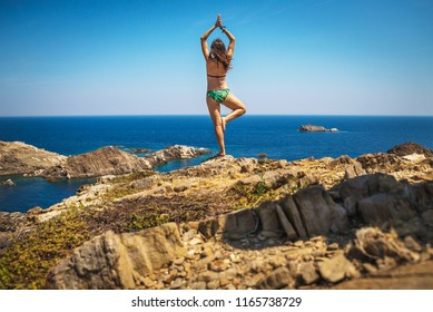 Athletic girl practicing yoga on a cliff above the sea. Healthy life