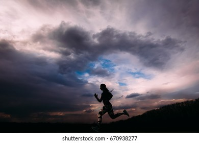 Athletic girl running and doing exercises Jogging on background of dark dramatic sky