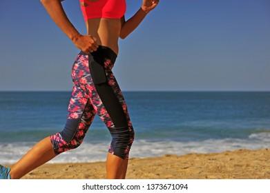 Athletic girl running on the summer beach
