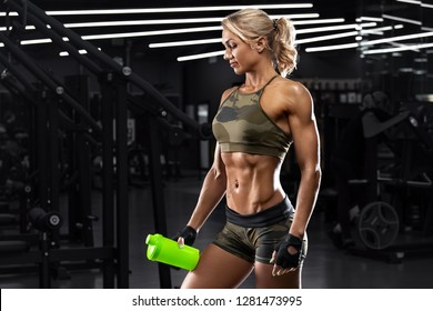 Athletic girl with shaker in gym. Fitness woman with flat belly, shaped abdominal, abs