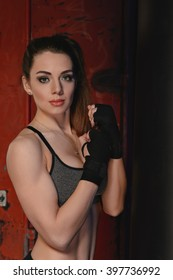 Athletic girl standing near a punching bag. Photographed in studio on a background of orange containers
