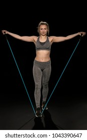 athletic girl stretches and exercises with a flexible rope