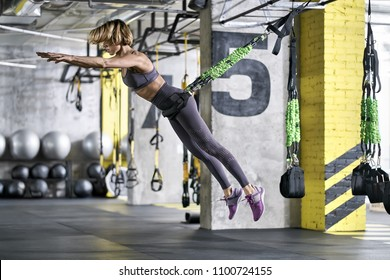Athletic girl is training with goflo-trainer in the gym. She is jumping in the air with outstretched arms. Woman wears a gray top and pants, violet sneakers. Horizontal.