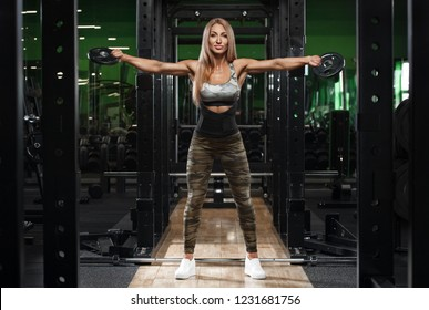 Athletic girl training shoulders at the gym, working out. Fitness woman exercising