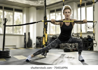 Athletic girl is training with a TRX Rip Trainer in the gym on the windows background. She wears a pants with patterns, black sleeveless and light sneakers. Woman looks forward with parted lips.