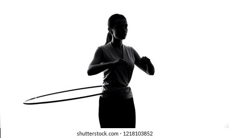 Athletic girl twisting hula hoop, exercising to lose weight, sports lifestyle