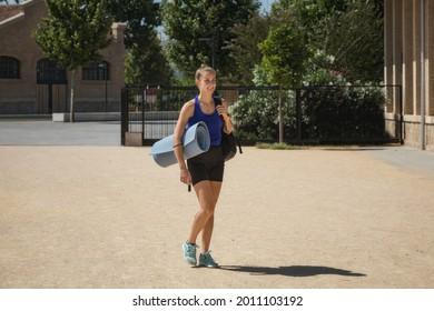 Niña atlética caminando con estera y bolsa de yoga. Plano entero y horizontal. Estilo de vida y deporte