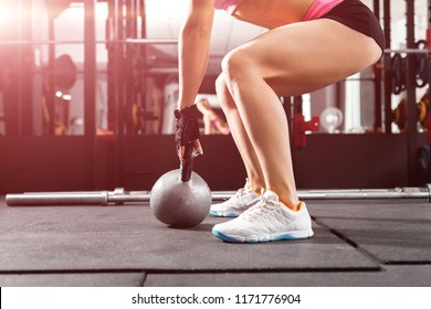 athletic girl wearing pink and black professional sportswear exercising with a kettlebell at the gym. Strength and motivation concept