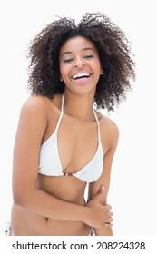 Athletic girl in white bikini smiling at camera on white background