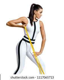Athletic girl working with resistance band. Photo of attractive latin girl with beautiful athletic body isolated on white background. Strength and motivation