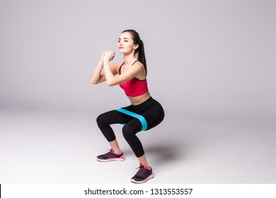 Athletic girl working with resistance band. Portrait of attractive girl with beautiful athletic body isolated on white background.