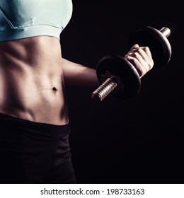 Athletic girl workout with dumbbells showing abs and muscles