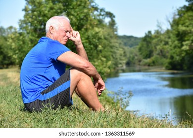 Athletic Grandfather Thinking Sitting By River