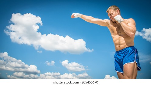 Athletic guy in blue shorts and boxing bandages fulfills kick exercising in nature