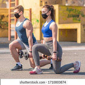 Athletic guy and a girl in medical masks lunges with dumbbells on a sports field during a pandemic. COVID-19. Health care.