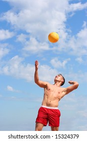 athletic guy playing volley-ball on the beach