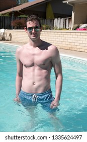 Athletic guy standing in an outdoor swimming pool with defined abs. Healthy and active man posing in a pool water up to his waist on a summer day. Confident man in a backyard pool looking at camera.