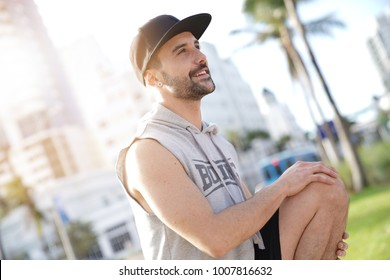 Athletic guy stretching outside after exercising