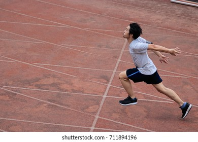 Athletic handsome young Asian runner sprinter crossing the finish line on track in stadium.