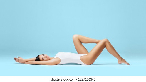 Athletic and healthy girl posing in white bodysuit. Fit and sexy woman in underwear swimsuit. Slim shape, nutrition, sport, fitness and diet concept.