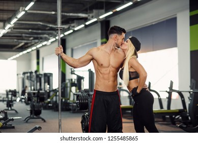 Athletic healthy man kisses his fitness girlfriend in the gym after training. Attractive strong man with barbell in hand and his girl near him.