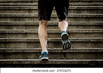 athletic legs of young sport man with sharp scarf muscles running on staircase steps jogging in urban training workout or runner competition in fitness and healthy lifestyle concept