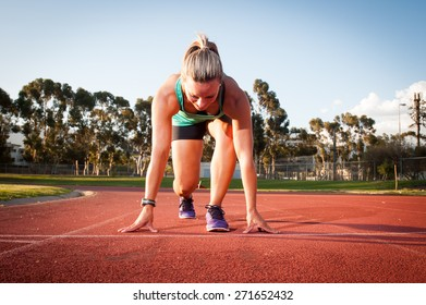 An athletic looking female runner on an outdoor track in summer