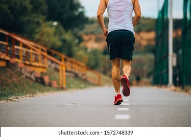 Athletic male exercising on a track outdoors while training jogging