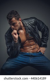 Athletic male model in a jeans and leather jacket over grey background.