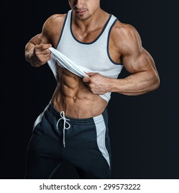 Athletic male model posing in sports clothing, pulling up tank top to reveal fit muscular abs. Isolated on black background. Closeup photo of an athletic guy with perfect abs