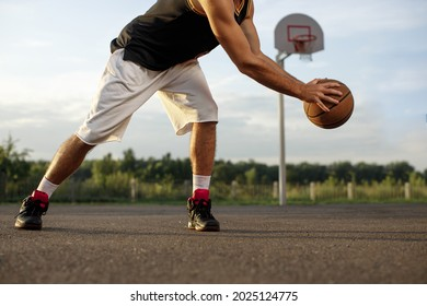 Athletic male playing basketball outdoors. Man dribbling ball at court