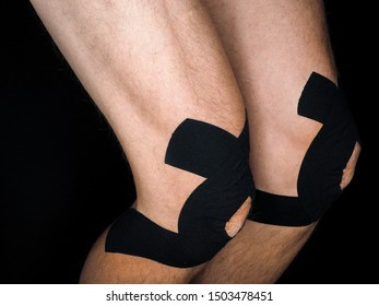 Athletic male with supporting sports tape over kneecaps, at close-up isolated on black