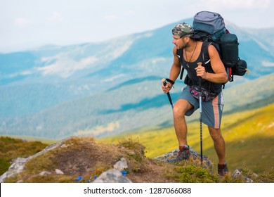 Athletic man is ascending mountain. Breathtaking scene is behind the traveler, going up on mossy stones with wildflowers.