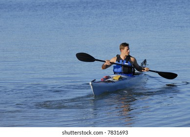 An athletic man is backing off the shore into calm blue waters of Mission Bay, San Diego, California. Copy space on top and left.