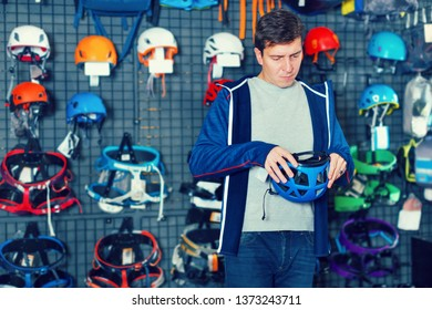 Athletic man buying climbing equipment in sporting goods store
