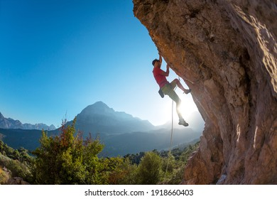Athletic man climbs an overhanging rock with rope, lead climbing. silhouette of a rock climber on a mountain background. outdoor sports and recreation