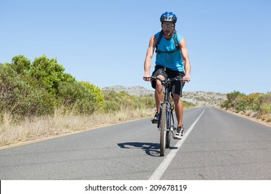 Athletic man cycling on open road on a sunny day